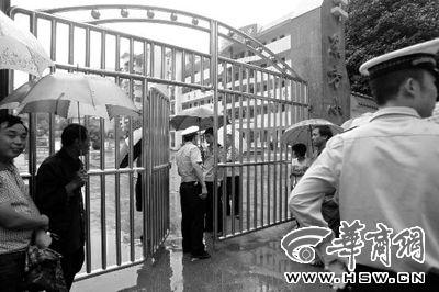 昨日,事发学校早已让学生回家,但很多学生的家长还是围在学校门口 华商报特派郧西记者 魏光敬 摄