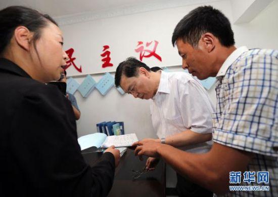 这是9月10日,张德江来到毕节双堰村村委会村民小组,仔细观看村小组日常工作记录,了解情况。
