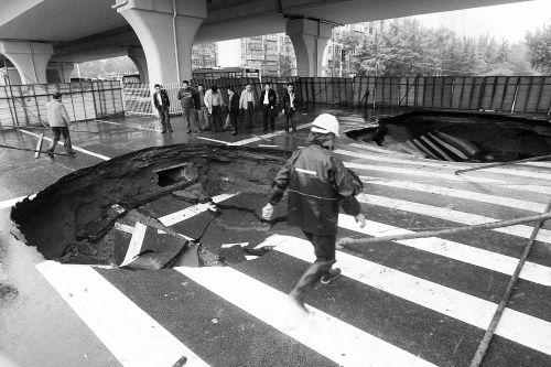 中原路西三环立交桥下由南向北原本4个车道,由于塌坑,而今3个车道被围挡 河南商报记者 张郁/摄
