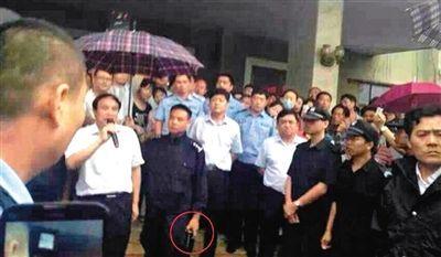 网友15日发帖称,河南获嘉县民众抗议污染企业。在领导与民众对话时,警察为其撑伞。