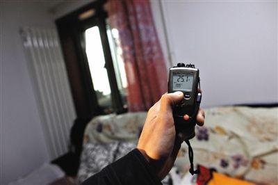 2014年11月15日,北蜂窝路15号院,工作人员在居民家中测量室内温度。新京报记者 薛珺 摄