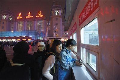 """昨日,北京站广场""""互联网取票窗口""""前部分乘客等待取票。昨日,北京四大火车站售票窗口开售春运火车票,购票乘客寥寥无几。 新京报记者 王嘉宁 摄"""