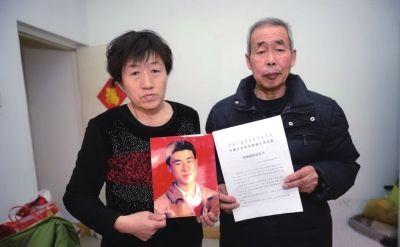 李三仁、尚爱云拿着儿子呼格吉勒图照片与《国家赔偿决定书》。中新社发