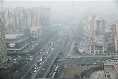 昨日,十里河桥、华威桥地区的楼群、车辆等笼罩在霾中。当日下午,市气象台发布霾黄色预警。中新社发 刘宪国 摄