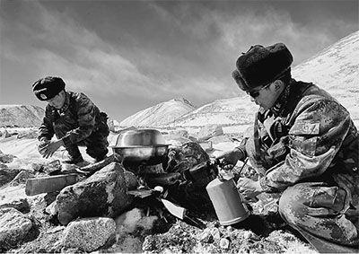 大年三十,西藏阿里高原气温骤降至零下21摄氏度,位于喜马拉雅山脉腹地的扎西岗边防连,按计划对海拔5580米的绒隆山口执行巡逻任务。图为边防连士官次仁顿珠(右)、王俊融雪烧水为巡逻分队准备午餐。 向文军摄(新华社发)
