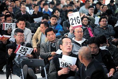 昨日,北京市昌平北七家,亚运村汽车交易市场,中央和国家机关公车改革取消车辆专场拍卖会,一位竞拍者举牌。新京报记者 薛珺 摄