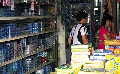 """朝阳区东郊市场一家日用杂货批发店,销售人员(右)在隐蔽处取出""""高仿""""洗发水卖给记者。新京报记者近日走访发现大量""""高仿""""日用品充斥市场。"""