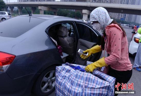 8月18日下午,天津港爆破现场左近的社区住民搬运生计用品分开。图为一名女人在简略防护后把生计品掏出轿车里。中新社发 贾国荣 摄