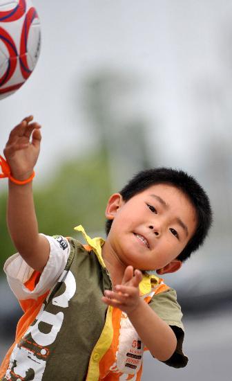 图文:男孩在绵阳九洲体育馆安置点外玩排球