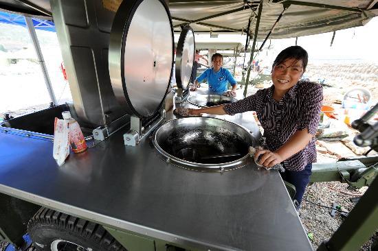 图文:村民在安置点清洁部队提供的野营炊事车