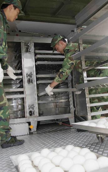 图文:战士在野战主食加工车上制作数码馒头