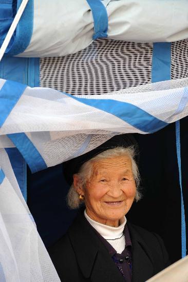 图文:80岁老人余怀秀站在自家帐篷的门口