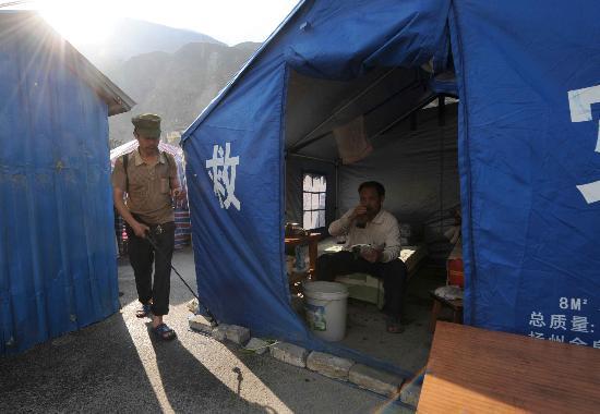 图文:受灾男子正在为帐篷营地喷洒消毒液