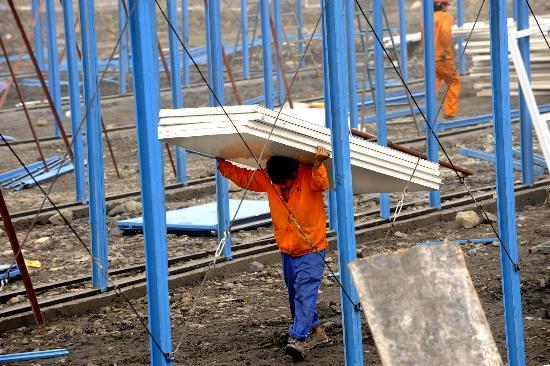 图文:工人正在施工点搬运活动板房建材
