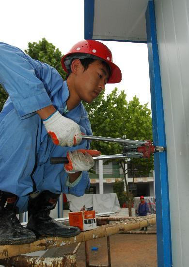 图文:一名工人正在陇南活动板房建设场地施工