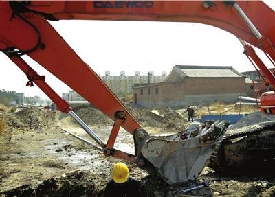 2009年,徐家拒绝拆迁,挖掘机在其门前施工。(资料图片) 本报记者朱嘉磊摄