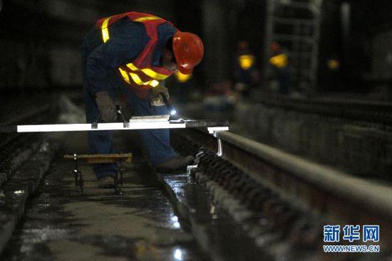 1月27日,工人在上海地铁4号线沉降段对抬升路轨进行最后的水平测试。
