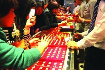"""昨天,南京新街口附近一家商场众多顾客挤在黄金柜台购买""""便宜了的金货""""。"""