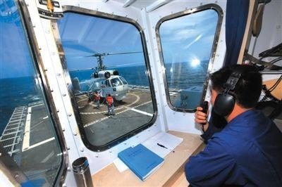 昨日,郑州舰塔台指挥员指挥舰载直升机准备起飞,执行海上反潜任务。新华社发