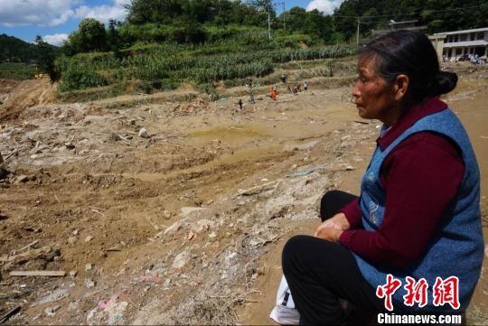 8月30日,73岁的周开秀顶着烈日,守候救援人员搜救自己的孙女。 王晶 摄