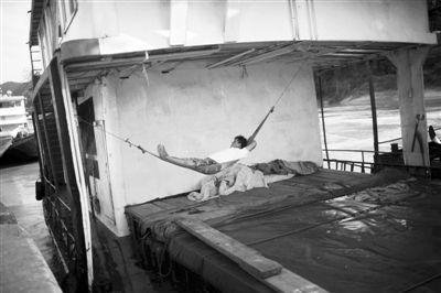 10月15日中午,西双版纳关累港,一名等待消息的船员躺在船后的吊床上。航道封闭后,留在船上的船员无所事事。摄影/本报记者 赵亢