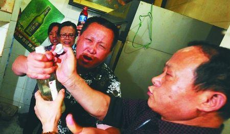 昨日,周渔府弹子石店,老板(左)抢夺执法人员手中一个装有白色液体的瓶子。