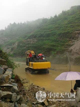 """6月3日,遵义务川县一条临时公路被淹,挖掘机载人""""过河""""。"""