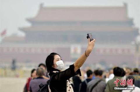 10月10日,一名游客在天安门前戴口罩自拍。