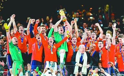 西班牙球员在南非世界杯领奖台上高举大力神杯庆祝; 这是2010年7月11