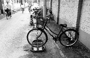 胡同看到,一辆自行车不仅上了锁,车主还把自行车和地锁锁在一起