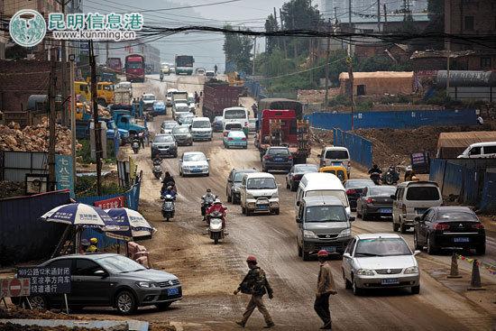 路过贵昆公路入城段的人和车都经历着波浪路和碎石路的洗礼。记者孟祝斌/摄