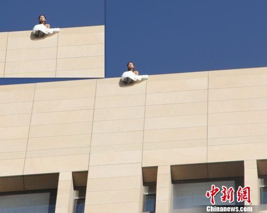 图为身着婚纱的女子坐在15楼楼顶。 王有德 摄
