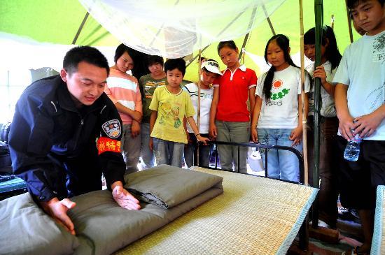 图文:杭州特警正在给儿童们示范叠被子