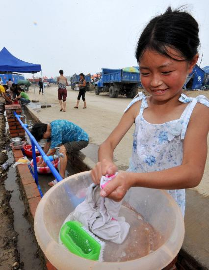 图文:清平小学学生在帐篷安置点自己洗衣服