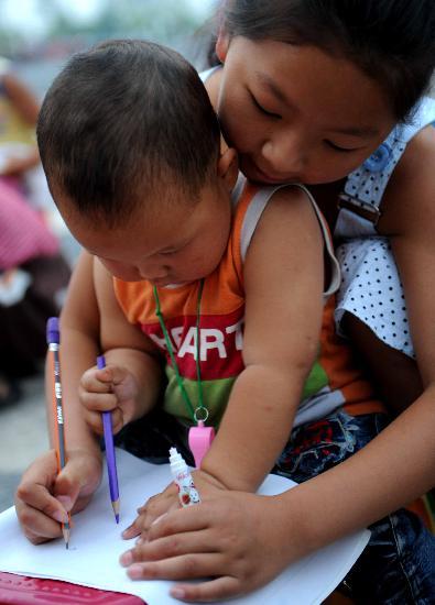 图文:10岁的朱诚在教两岁的刘星雨画画