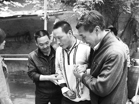 赵利强(左)和王常安(右)扶着王锋做康复训练
