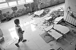 昨日中午,海淀区明光村一家幼儿园内墙体被拆,一名孩子仍在边上玩耍。本报记者 杨杰 摄
