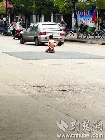 小孩跪在马路上