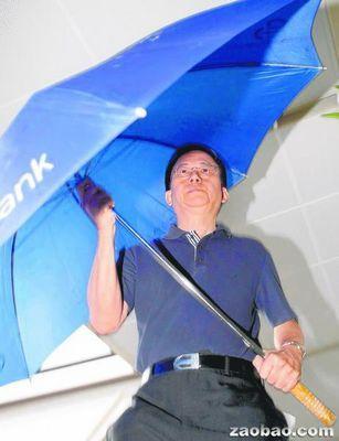 新加坡华人医生王腾吉个子不高,撑着大伞离开法庭。(新加坡《联合早报》援引海峡时报)