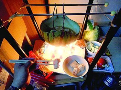 两张椅子被面对面叠在一起,穿了两根线的西瓜皮就悬空在椅脚中间,下面有蜡烛加热,这就是西瓜火锅。