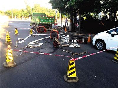 昨天,北湖渠路,环卫团体已将排污水所用的水龙带移除,并对井口封锁。新京报记者 饶沛 摄