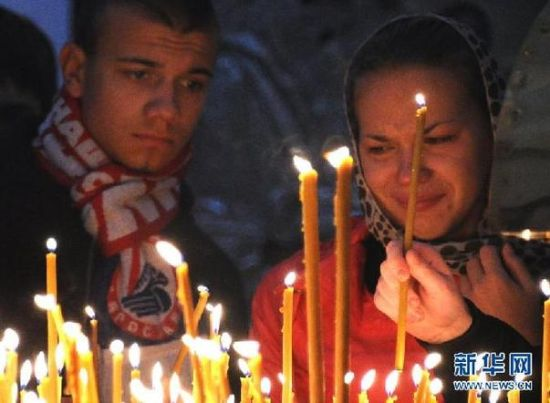 9月8日,在俄罗斯雅罗斯拉夫尔的一个教堂,人们在为坠机遇难者举行的悼念仪式上点燃蜡烛。据报道,一架雅克-42型客机7日在俄罗斯西部雅罗斯拉夫尔州坠毁,导致43人死亡。 新华社/法新