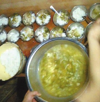 """▲7月17日中午,长沙市金帆幼儿园的生活老师正在给孩子们分餐。菜是水煮黄瓜和水煮包菜,里面掺杂了少许肉末。老师说,""""吃得太油,对孩子不好""""。"""