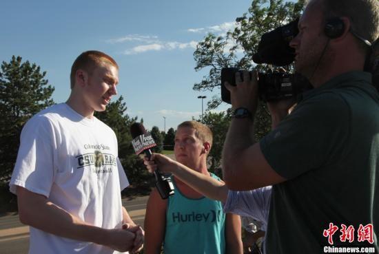 地时间7月20日,两名枪击案目击者安卓・鲍沃斯(左)和兰斯・巴内斯接受美国福克斯新闻电视台采访。中新社发 王欢 摄