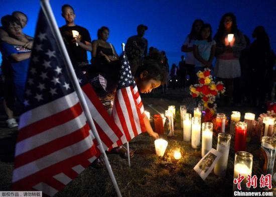 当地时间7月20日,美国科罗拉多州奥罗拉市,一位四岁的小女孩将蜡烛放置在悼念枪击案遇难者的草坪上,为遇难者守夜祈福。