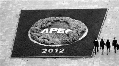 5日,符拉迪沃斯托克,几名志愿者经过APEC峰会媒体中心前的花园。