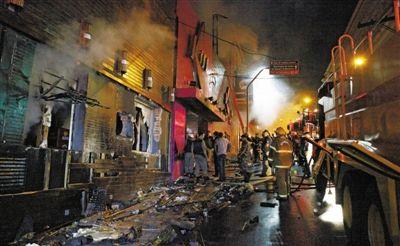 27日凌晨,巴西南里奥格兰德州圣玛丽亚市一家夜总会突发大火,造成至少245人死亡。图为消防人员正在现场灭火救援。