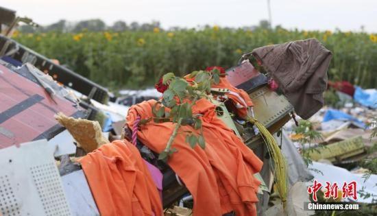 几件世界杯荷兰队球衣挂在马航失事客机的一处残骸上,附近居民在上面放上了一朵鲜花。17日,一架马来西亚航空公司的波音777客机在靠近俄罗斯边界的乌克兰东部地区坠毁,机上乘客和机组成员共298人全部遇难。中新社发 王修君 摄