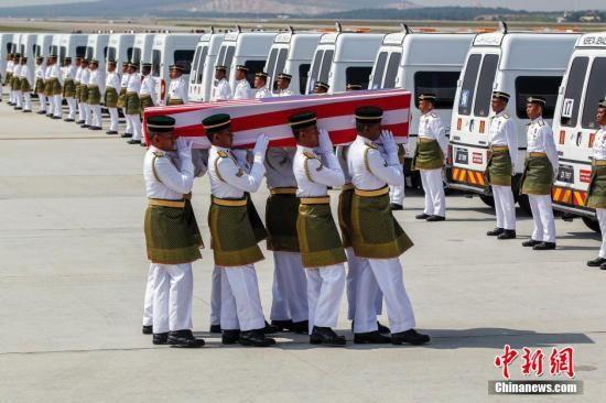 马航MH17首批马来西亚籍罹难者遗体8月22日运返吉隆坡,马来西亚举行隆重仪式迎接。图为马来西亚仪仗兵在吉隆坡国际机场将遗体抬向灵车。中新社发 赵胜玉 摄