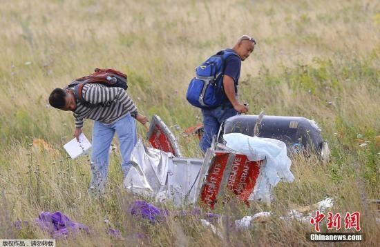 资料图:当地时间2014年7月22日,乌克兰顿涅茨克地区,亲俄武装、欧安组织成员以及一支马来西亚空难调查团在坠机现场勘查。